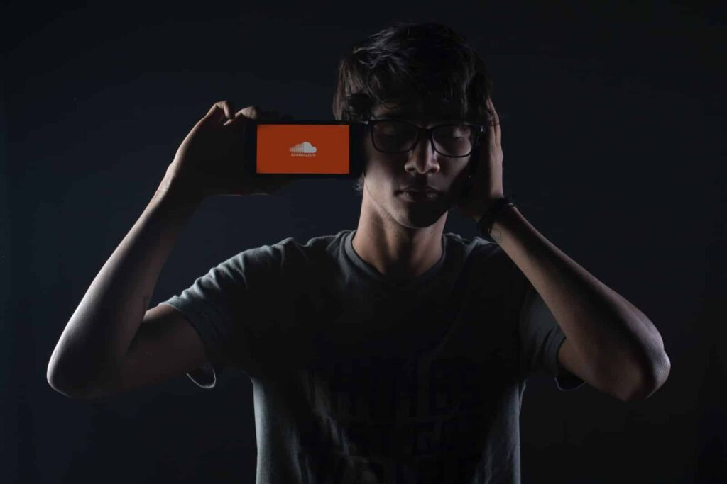 man listening to Soundcloud music on smartphone